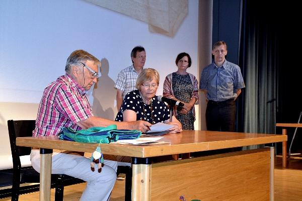 Aarne Haapakosken tytär Kristiina Hakala ja hänen miehensä Tapani Hakala allekirjoittamassa kirjailijan arkiston luovutusasiakirjoja Taustalla aineiston vastaanottavan Pieksämäki-seuran edustajat sekä Aarne Haapakoski-seuran edustaja.